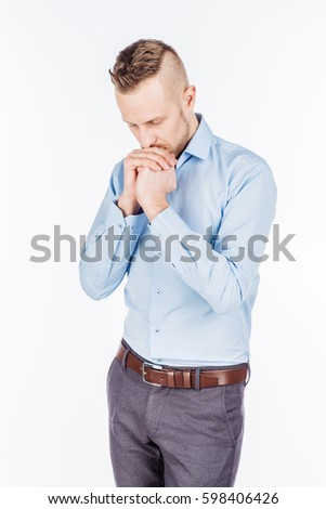 portrait of bearded business man praying with hands. human emotion expression and lifestyle concept. image on a white studio background.