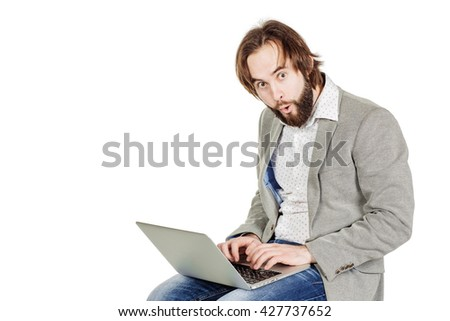 portrait of bearded business man working on his laptop and looking at camera. emotions, facial expressions, feelings, body language, signs. image on a white studio background. - stock photo