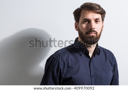 Portrait of bearded businessman in dark blue shirt standing against empty white wall - stock photo