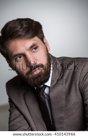 Portrait of bearded businessman in suit on grey background
