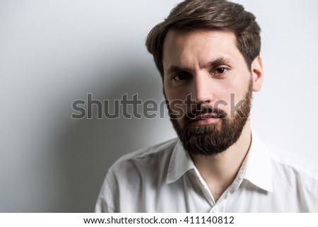 Portrait of bearded businessman in white shirt with collar