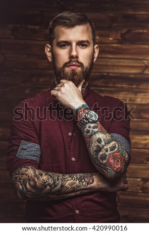 Portrait of bearded man in red shirt with tattooe on his arms.