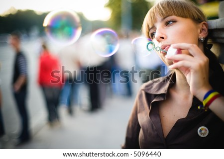Portrait of beauriful model blowing bubbles (street photo) - stock photo