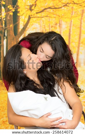 portrait of beautiful affectionate lesbian couple holding their baby over forrest background - stock photo