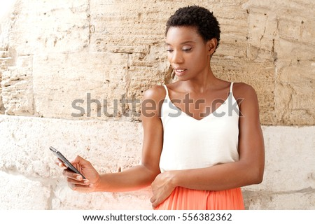 Portrait of beautiful african american smart woman leaning on a textured stone wall in old city destination, using a smart phone to network, sunny outdoors. Technology travel recreation lifestyle.