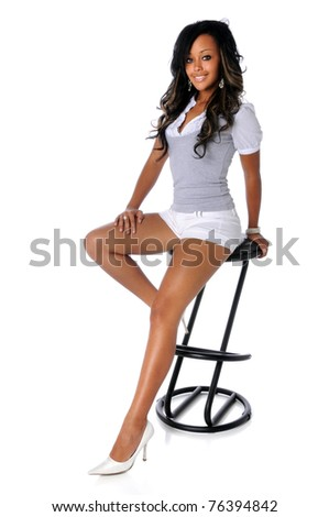 Portrait of beautiful African American woman sitting on stool isolated over white background
