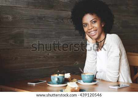 Portrait of beautiful African American woman with Afro haircut wearing trendy clothes, looking and smiling at the camera, showing white teeth with braces, leaning her elbow on the wooden table - stock photo