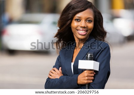portrait of beautiful african news reporter standing outdoors - stock photo