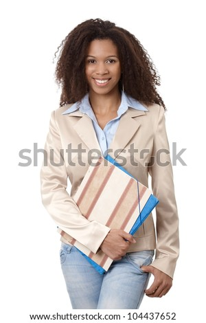 Portrait of beautiful afro-american woman holding folders, smiling. - stock photo