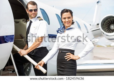 Portrait of beautiful airhostess with pilot boarding private jet - stock photo