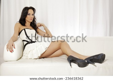 Portrait of beautiful and attractive young adult sensuality and sexy female brunette woman posing in white and black dress on the sofa - stock photo