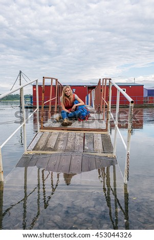 Portrait of beautiful and cheerful girl with backpack sitting on wooden bridge party in water against of cloudy sky.Copy space - stock photo