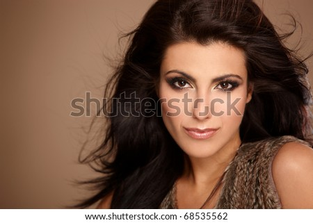 Portrait of beautiful and sexy woman looking at camera, isolated on beige - stock photo
