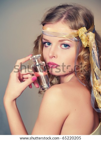 Portrait of beautiful and sexy woman with perfume bottle, retro style