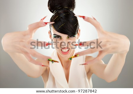 portrait of beautiful angry brunette girl shows her finger nail make up - stock photo