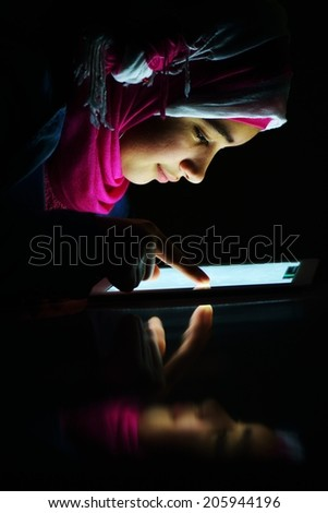 Portrait of beautiful Arabic Muslim girl using tablet - stock photo