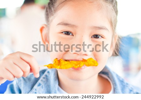 Portrait of beautiful asean girl, she is eating, Thailand. - stock photo