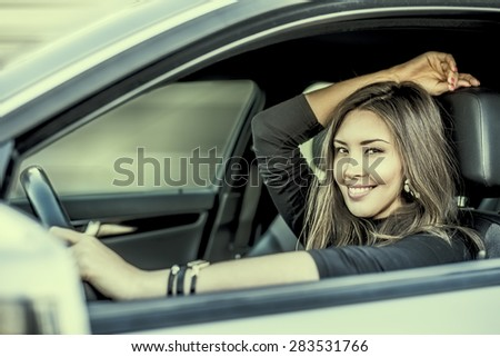 Portrait of beautiful asian brunette young woman keep wheal inside new luxury car through transparent window background Copy space for inscription Taxi Girl Empty place Female rest indoor Smiley face