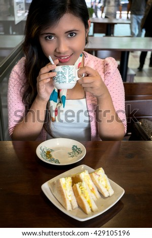 Portrait of beautiful asian college girl student sitting on campus cafe, breakfast with coffee and sandwish, smile, feel relax and enjoy - stock photo