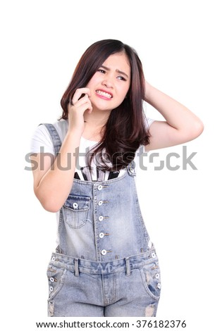 Portrait of beautiful Asian girl talking on cellphone with frustrated face, isolated on white background - stock photo