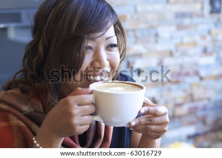 Portrait of beautiful Asian woman drinking cappuccino at a coffee shop. - stock photo