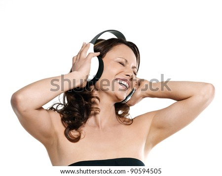 Portrait of beautiful Asian woman enjoying music in studio isolated on white background - stock photo