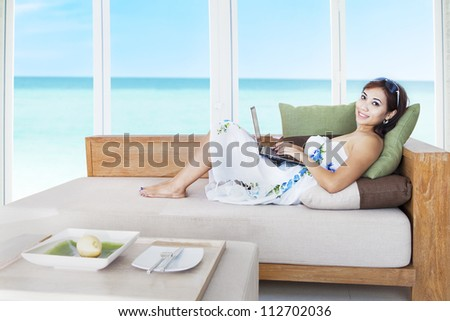 Portrait of beautiful asian woman lying on the couch with laptop and ocean view on the window - stock photo