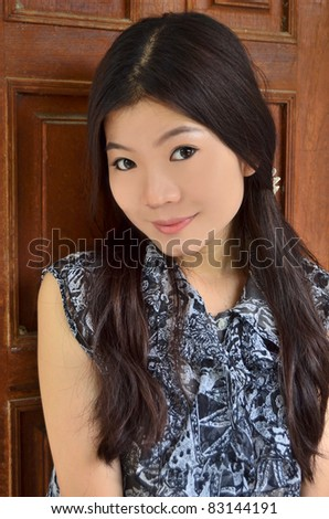 Portrait of beautiful asian woman on wood background - stock photo