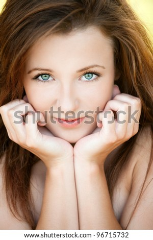 Portrait of beautiful attractive young woman propping up her face with hands at summer green park - stock photo