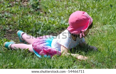 Portrait of beautiful baby girl lying on the grass - stock photo