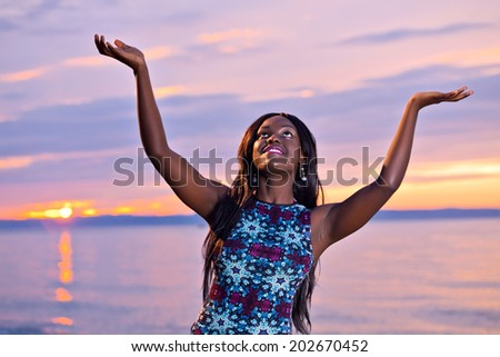 Portrait of beautiful black African American woman posing with open hands up to the sky on the beach at sunset - stock photo