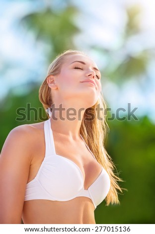 Portrait of beautiful blond girl on the beach with closed eyes of pleasure enjoying sunny day, sexy model wearing stylish white swimsuit, fashion of summer time - stock photo
