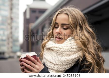Portrait of beautiful blond girl walking down the street. Keeping takeaway drink. Urban city scene. Outdoors - stock photo