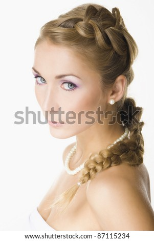 Portrait of beautiful blond girl with creative braid hairdo and pearls - stock photo