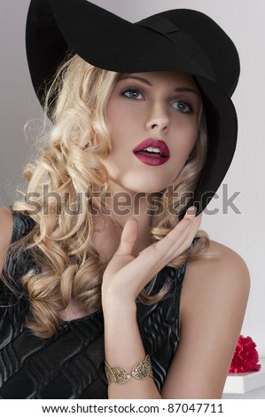 portrait of beautiful blond girl with curly hair and hat with black dress - stock photo