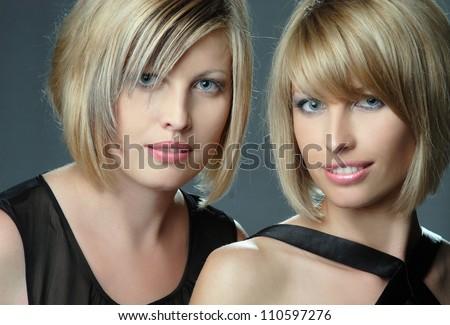 portrait of beautiful blond twin sisters - stock photo