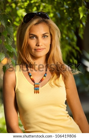 Portrait of beautiful blond woman at summertime in the garden.