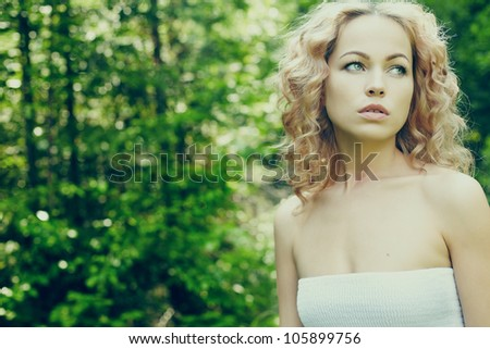Portrait of beautiful blond woman in fairy forest - stock photo
