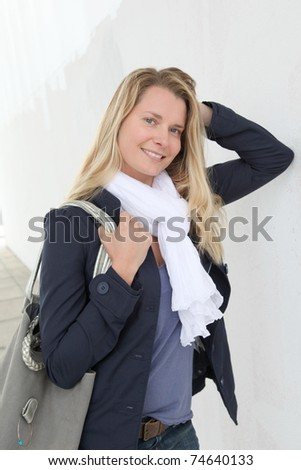 Portrait of beautiful blond woman in town - stock photo