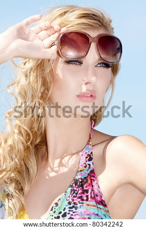 portrait of beautiful blonde girl in sunglasses on background blue sky