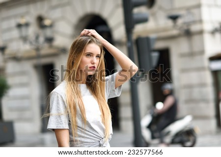 Portrait of beautiful blonde girl in urban background - stock photo