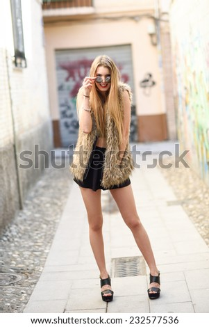 Portrait of beautiful blonde girl in urban background smiling and playing with her sunglasses