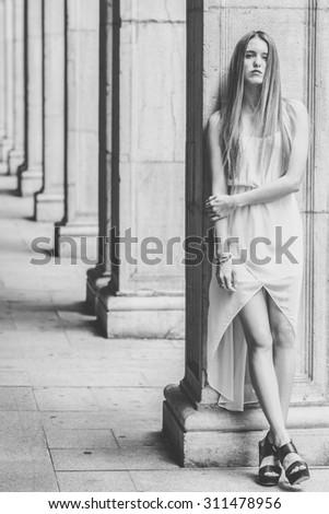 Portrait of beautiful blonde girl in urban background wearing white dress - stock photo