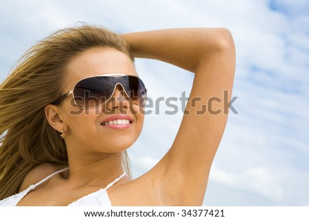 Portrait of beautiful blonde in sunglasses looking aside