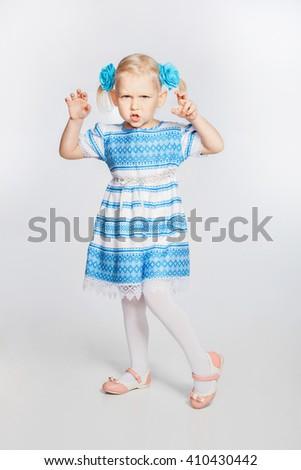 Portrait of beautiful blonde little girl. Girl grimaces - stock photo