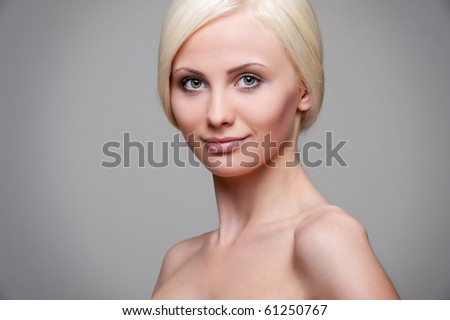 portrait of beautiful blonde over grey background - stock photo