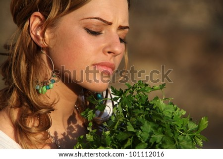 portrait of beautiful blonde smiling girl with vegetables and herbs