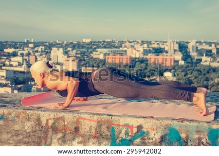 Portrait of beautiful blonde strong woman in sportwear doing workout push-ups on the roof of a skyscraper above the big city at early morning. Female sporty muscular body. Sunrise bright sunny light. - stock photo