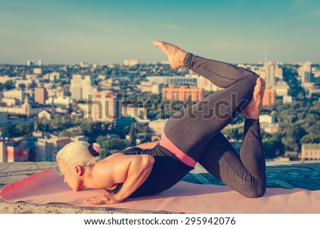Portrait of beautiful blonde strong woman in sportwear doing workout yoga exercise on the roof of a skyscraper above the big city at early morning. Female sporty muscular body. Sunrise sunny light. - stock photo