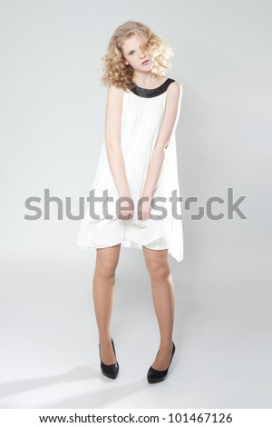 Portrait of beautiful blonde teenage girl in white dress over gray - stock photo